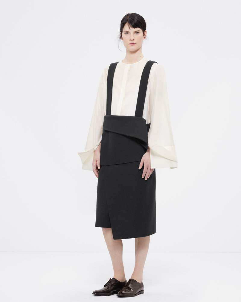 Re-proportioned collarless shirt with layered cuffs in off-white and a wool wrap skirt with suspenders in black